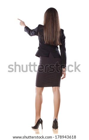 rear view of young business woman pointing with her finger on empty space - stock photo
