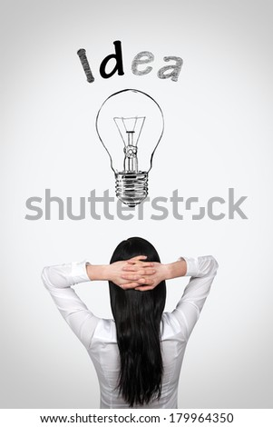 Rear view of young business woman thinking of her ideas with hands behind head - stock photo