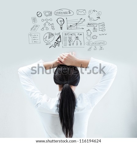 Rear view of young business woman thinking of her plans with hands behind head - stock photo