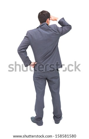 Rear view of young businessman looking away on white background