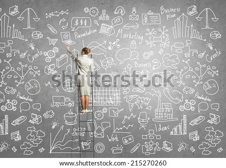 Rear view of young businesswoman standing on ladder - stock photo
