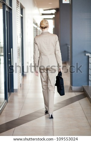 rear view of young businesswoman walking to office - stock photo