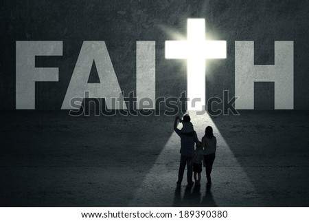 Rear view of young christian family walking toward faith door - stock photo