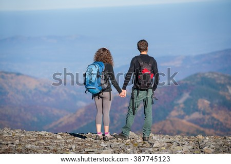 Rear view of young couple hikers with backpacks standing on the ridge of the mountain, enjoying the view of beautiful open overlook on the mountains. Couple is holding hands. Sunny autumn day.