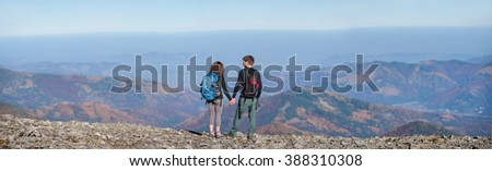 Rear view of young couple hikers with backpacks standing on the ridge of the mountain, enjoying the panorama view of beautiful open overlook on the mountains. Couple is holding hands. Wide angle view - stock photo
