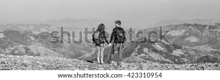 Rear view of young couple hikers with backpacks standing on the ridge of the mountain, enjoying the panorama view. Couple is holding hands. Wide angle view. black and white - stock photo