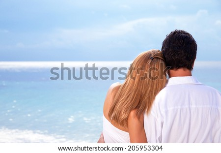 Rear view of young couple hugging on the beach, honeymoon on Maldives, enjoying wonderful seaview, love concept  - stock photo