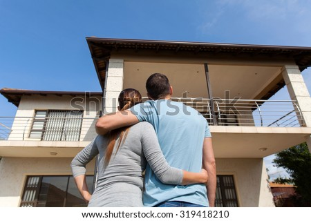 rear view of young couple looking at their new house - stock photo