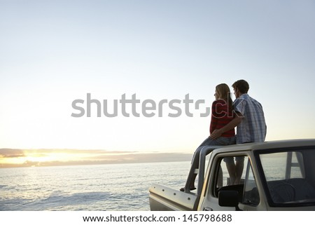 Rear view of young couple on pick-up truck parked in front of ocean enjoying sunset - stock photo