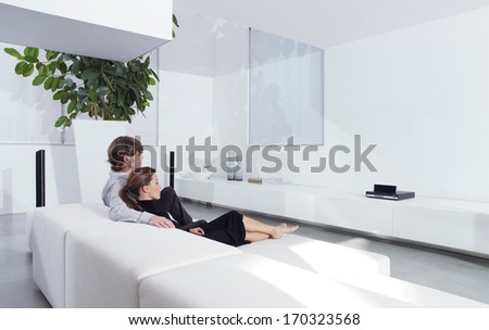 Rear view of young couple on sofa watching TV in living room  - stock photo