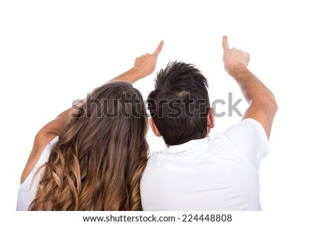 Rear view of young couple sit on ground back and point somewhere, full length portrait isolated on studio white background. - stock photo