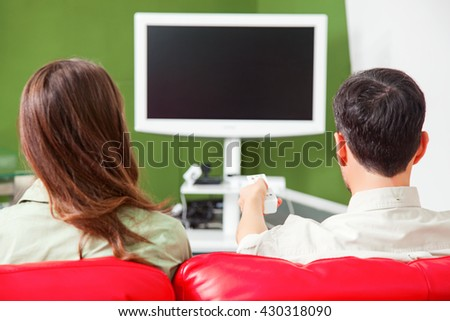 Rear view of young couple watching TV. Male and female partners are sitting on red sofa. They are at home. - stock photo