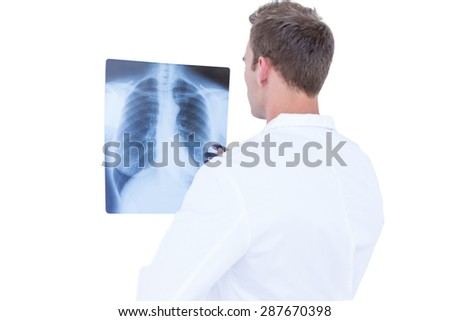Rear view of young doctor looking at x-ray on white background