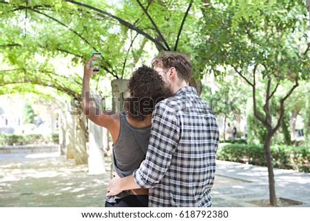 Rear view of young ethnically diverse tourist couple hugging, using smart phone to take pictures, visiting romantic park on summer holiday, outdoors. Man and woman using technology taking photos.