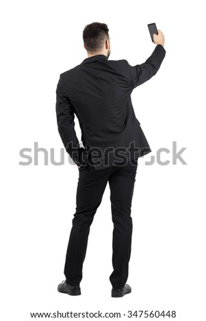 Rear view of young executive in black suit taking photo with his cellphone.  Full body length portrait isolated over white studio background.