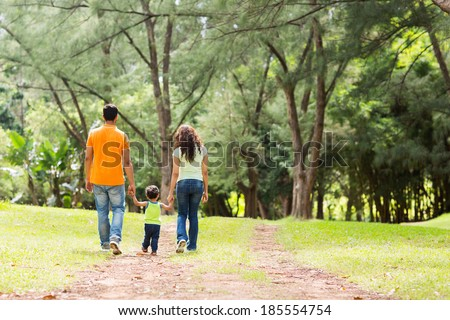 rear view of young family holding hands walking in forest - stock photo