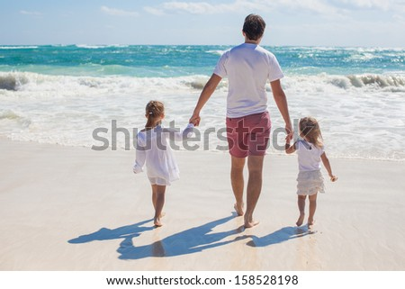 Rear view of Young father and his adorable little daughters walking on white sand beach in sunny day - stock photo