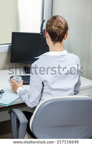 Rear view of young female customer service agent working at desk in call center - stock photo