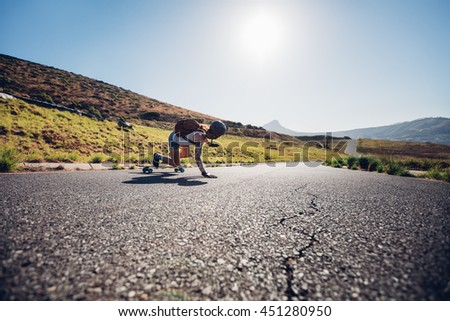 Rear view of young female skater practicing skateboarding on rural roads on a sunny day. She is doing stunts and touching the road. - stock photo