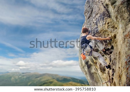 Rear view of young girl climber climbing with rope and carbines on a big rocky wall on high altitude against blue sky and mountains. Summer time. Climbing equipment.