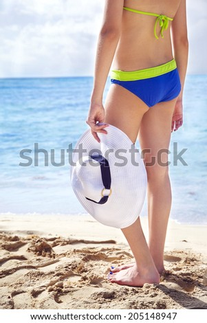 Rear view of young girl in bikini and hat. Focus on hand with hat