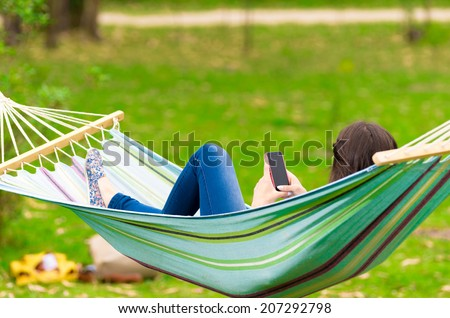 rear view of young girl lying on a hammock looking at her cell phone - stock photo