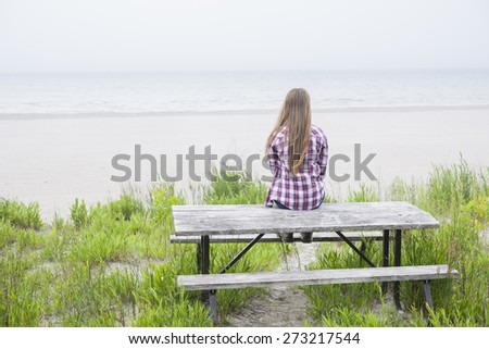 Rear view of young girl with long blond hair sitting on old beach picnic table facing ocean wearing plaid shirt - stock photo