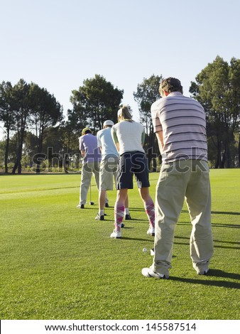Rear view of young golfers standing in row teeing off on golf course - stock photo