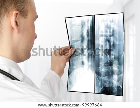 Rear view of young male doctor examining a xray