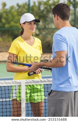 Rear view of young man and woman couple playing tennis or having tennis lesson - stock photo