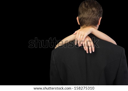 Rear view of young man being hugged by his wife on black background - stock photo