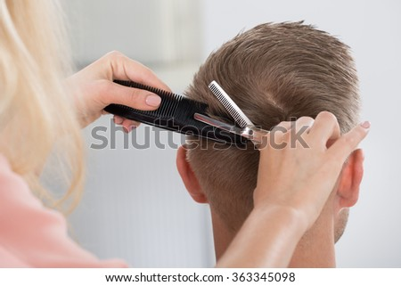 Rear view of young man getting haircut from female hairdresser at salon