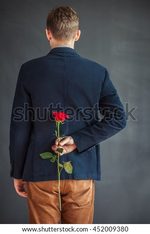 Rear view of young man holding red rose behind his back. Surprise - stock photo