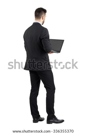 Rear view of young man in suit using laptop.  Full body length portrait isolated over white studio background.  - stock photo