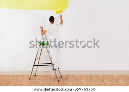 Rear view of young man painting wall with yellow paint roller at home - stock photo