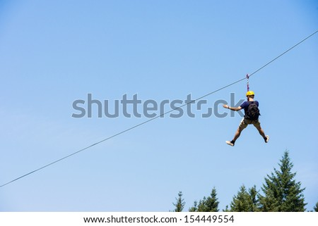 Rear view of young man riding on zip line against blue sky - stock photo