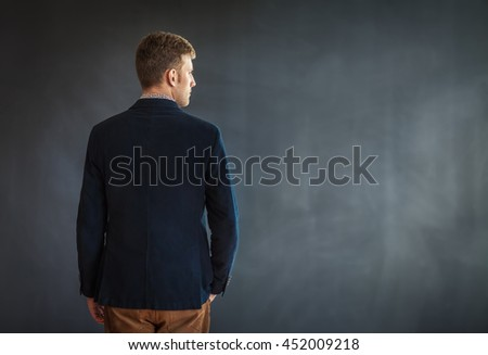 Rear view of young man standing against grey wall background with copy space - stock photo