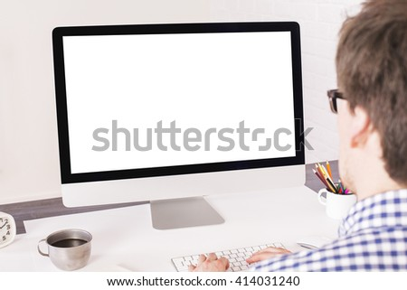 Rear view of young man typing on keyboard in front of a blank computer screen. Mock up - stock photo