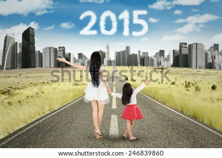 Rear view of young mother and daughter walking on the road while holding hands with numbers 2015 on the sky - stock photo
