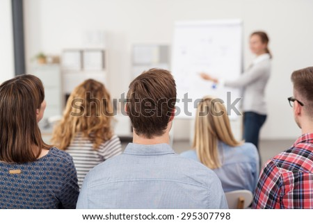 Rear View of Young Office Workers in Casual Outfits Listening to a Top Manager Explaining Something Using Illustrations. - stock photo