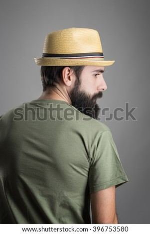 Rear view of young serious bearded man with straw hat looking away. Headshot portrait over gray studio background with vignette.  - stock photo