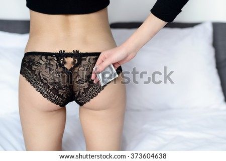 Rear view of young sexy woman holding a silver condom packet in her hand. Wearing black panties