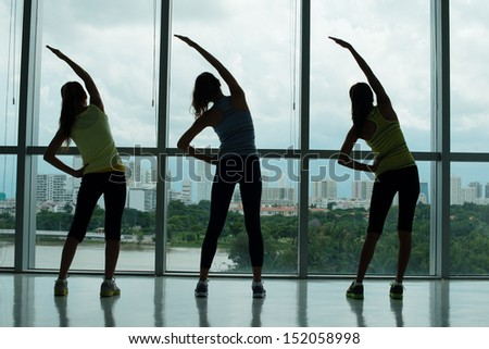 Rear view of young sportswomen doing bending exercises in the aerobics class