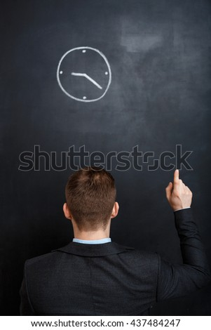 Rear view of young, suited business man looking at clock painted on blackboard