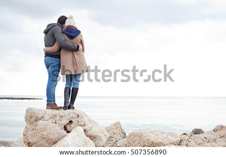 Rear view of young tourist couple together on textured rocks in destination beach on a winter holiday with coats, looking ahead contemplating the sea, hugging outdoors. Travel lifestyle exterior.