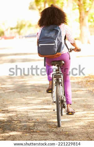 Rear View Of Young Woman Cycling Along Street To Work - stock photo