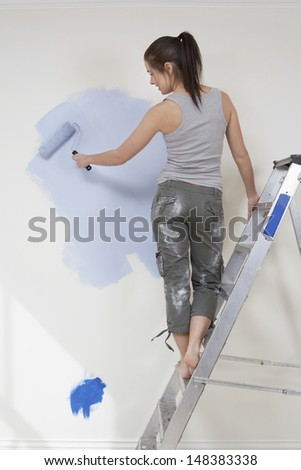 Rear view of young woman painting wall with paintroller while standing on stepladder at home - stock photo