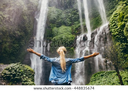 Rear view of young woman standing in front of waterfall with her hands raised. Female tourist with her arms outstretched looking at waterfall. - stock photo