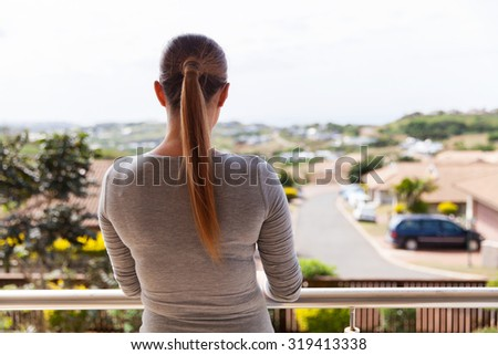 rear view of young woman standing on balcony at home - stock photo