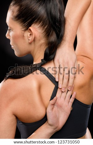 Rear view of young woman stretching her arms and back - stock photo